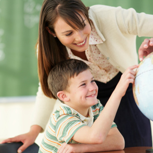 Teacher and boy (8-9) looking at globe in classroom