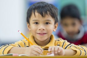 A multi-ethnic group of elementary students are sitting at their desks on their first day back to school. One boy is smiling and looking at the camera.